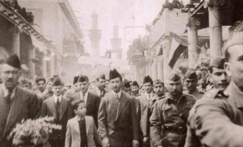 الامير عبد الاله يمسك بيد الملك فيصل اثناء تجوالهم في مدينة كربلاء المقدسة سنة 1945 Ooa__o10