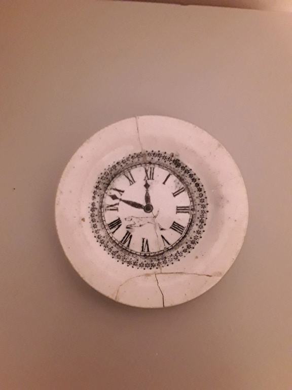 Small plate with clock face and dog in middle. 20200417