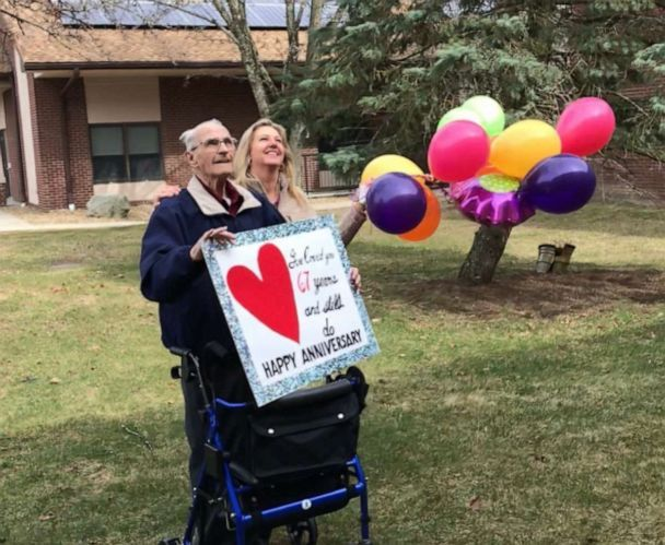 Husband holds sign for wife outside nursing home on 67th anniversary after they ban visitors  A051a110
