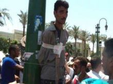 ثوار ميدان التحرير يمسكون ببلطجي ويعلقونه على أحد أعمدة الساحة 571510
