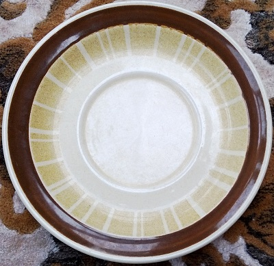 Rimmed saucer with radiating 'spokes' and a brown band. No_nam16