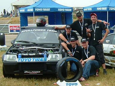 Le Team FPT à côté du 205 T16 FPT devant le stand TOYO