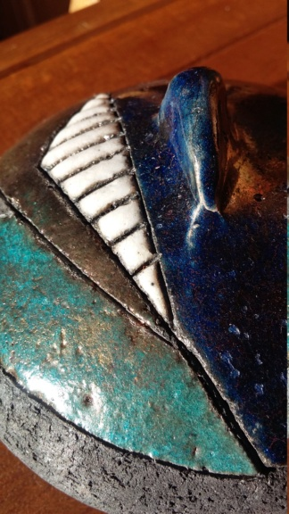 Small lidded dish some iridescence to glaze dark ceramic signed T. T ..L? 20190116