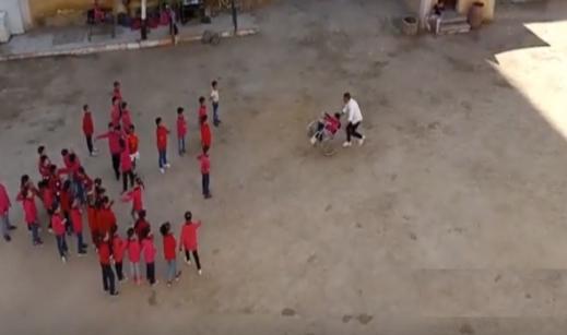 إنسانية معلم بسوهاج..  يساعد طالب معاق على اللعب مع زملائه بكرسيه المتحرك 8555